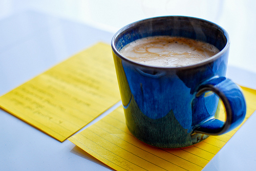 Blue cup of coffee on top of yellow note paper