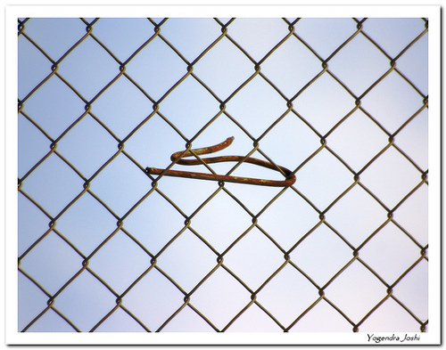 Chain-link fence with short wire warped around several links